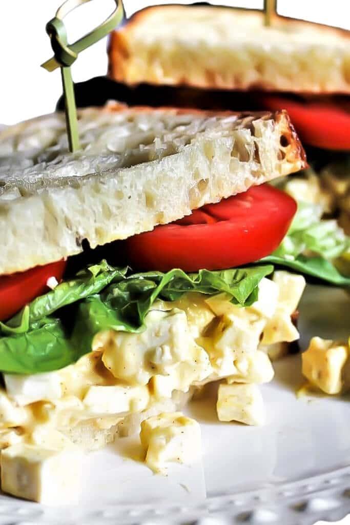 Un primer plano de un sándwich de ensalada de huevo de tofu con lechuga y tomate.