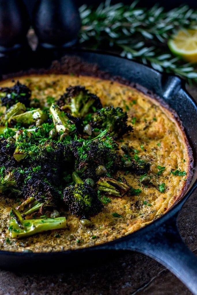 Farinata con brócoli carbonizado y alcaparras al limón en una sartén de hierro.
