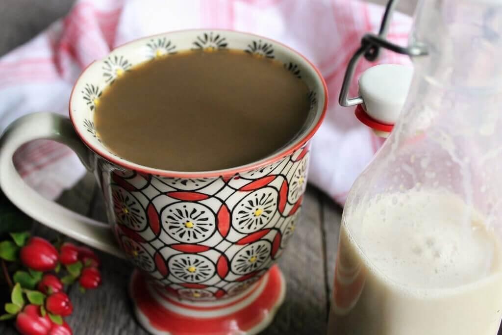 Una colorida taza de café llena de café con crema de soja añadida con un tarro de cristal lleno de crema vegana.