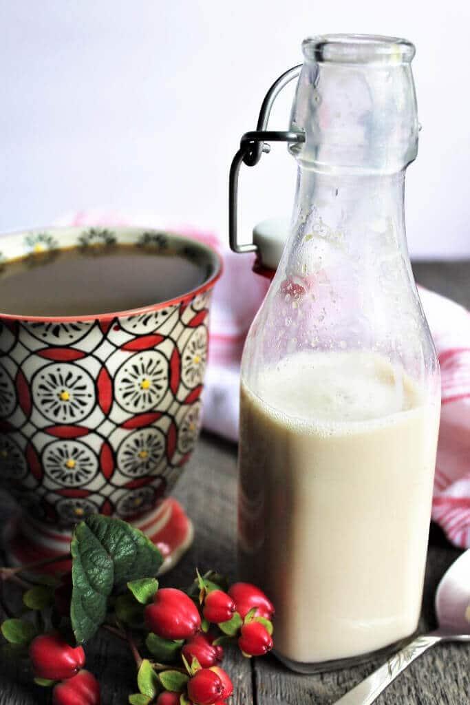 Un bote de cristal lleno de crema de soja casera junto a una taza de café.