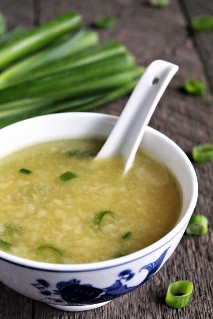 Sopa vegana de gotas de huevo en un bol blanco con cebollas verdes detrás.