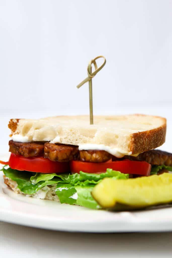 Un sándwich BLT vegano hecho con bacon de tempeh en un plato blanco con un pepinillo al lado.