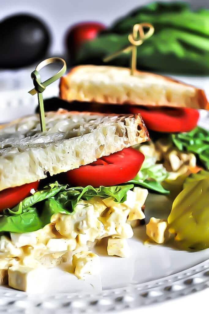 Un sándwich vegano de ensalada de huevo hecho con tofu con una rodaja de tomate y lechuga.
