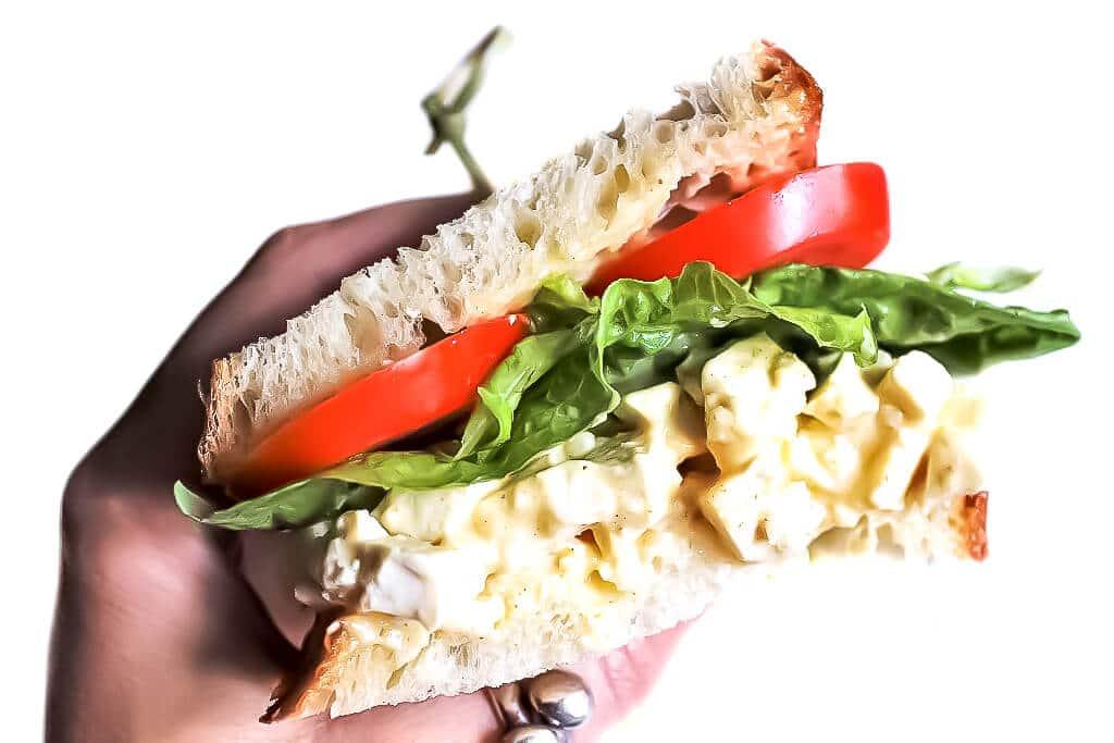 Un sándwich de ensalada de huevo de tofu vegano en la mano de alguien listo para darle un mordisco.