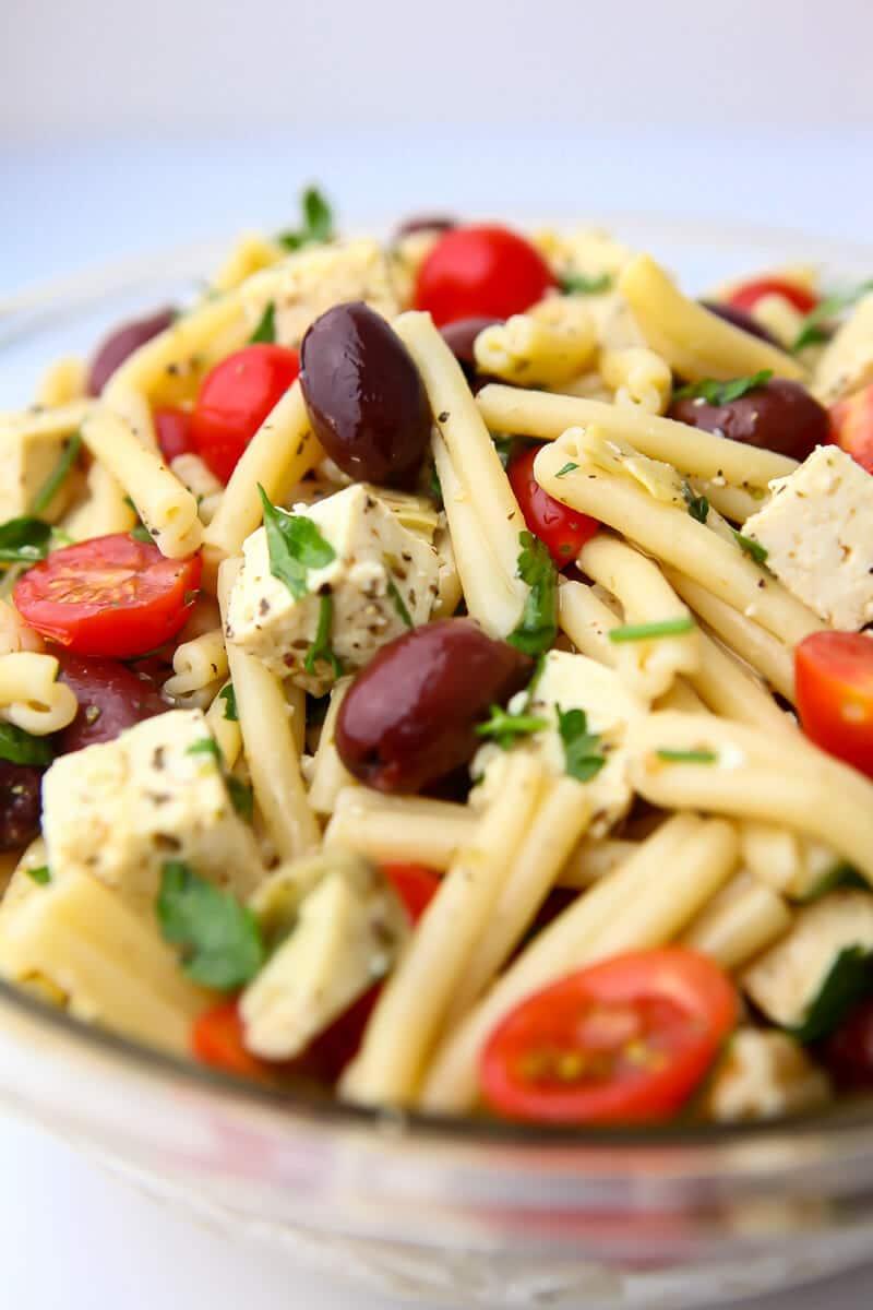 Un bol de cristal lleno de ensalada de pasta griega vegana con tofu feta vegano, tomates, aceitunas y hierbas.