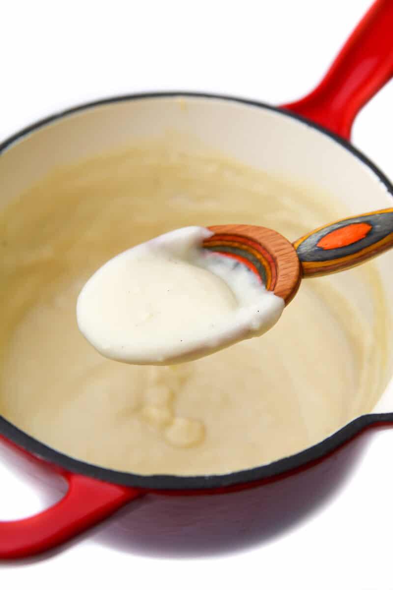 Una cacerola roja con salsa bechamel vegana sobre una colorida cuchara de madera.