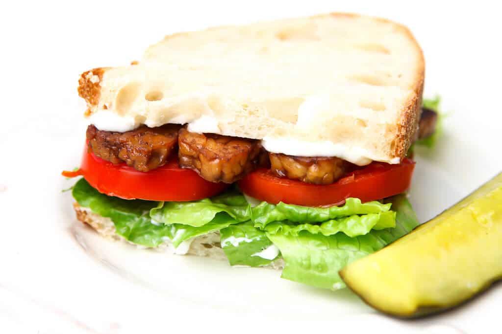 Un sándwich BLT vegano hecho con bacon de tempeh con un pepinillo al lado.