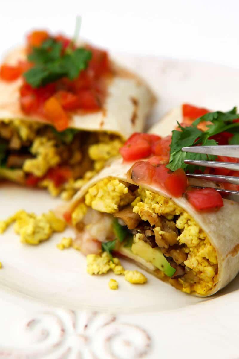 Un burrito de desayuno vegano cortado por la mitad con salsa encima y un tenedor cortando en él.
