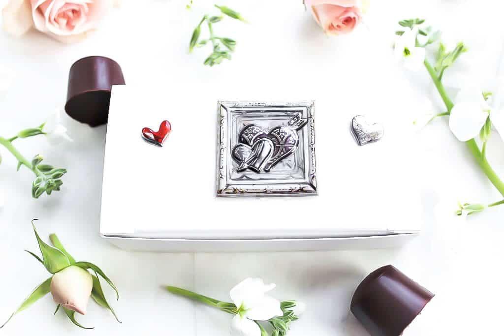 Una caja de bombones blanca llena de chocolates con flores alrededor.