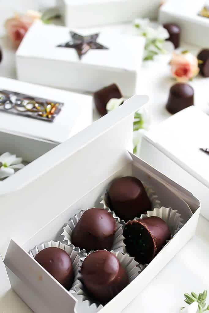 Una caja abierta de chocolates caseros sin leche y más cajas bonitas de chocolate blanco detrás.
