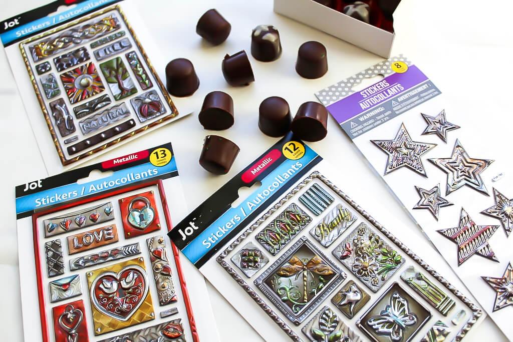 Un surtido de pegatinas metálicas compradas en The Dollar Tree utilizadas para decorar cajas de caramelos para hacer cajas de regalo.