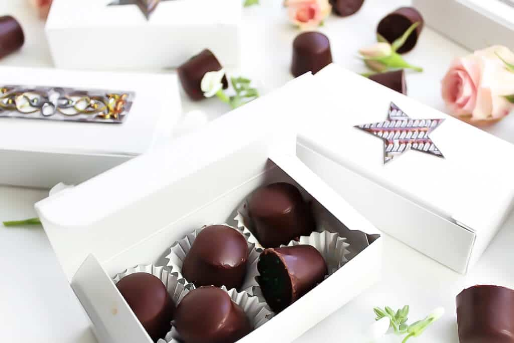 Una caja de caramelos blanca llena de chocolates caseros.