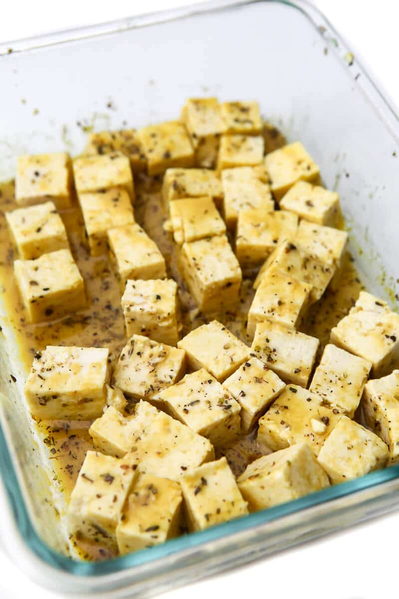 Un plato de cristal poco profundo lleno de tofu marinado en el adobo de feta.