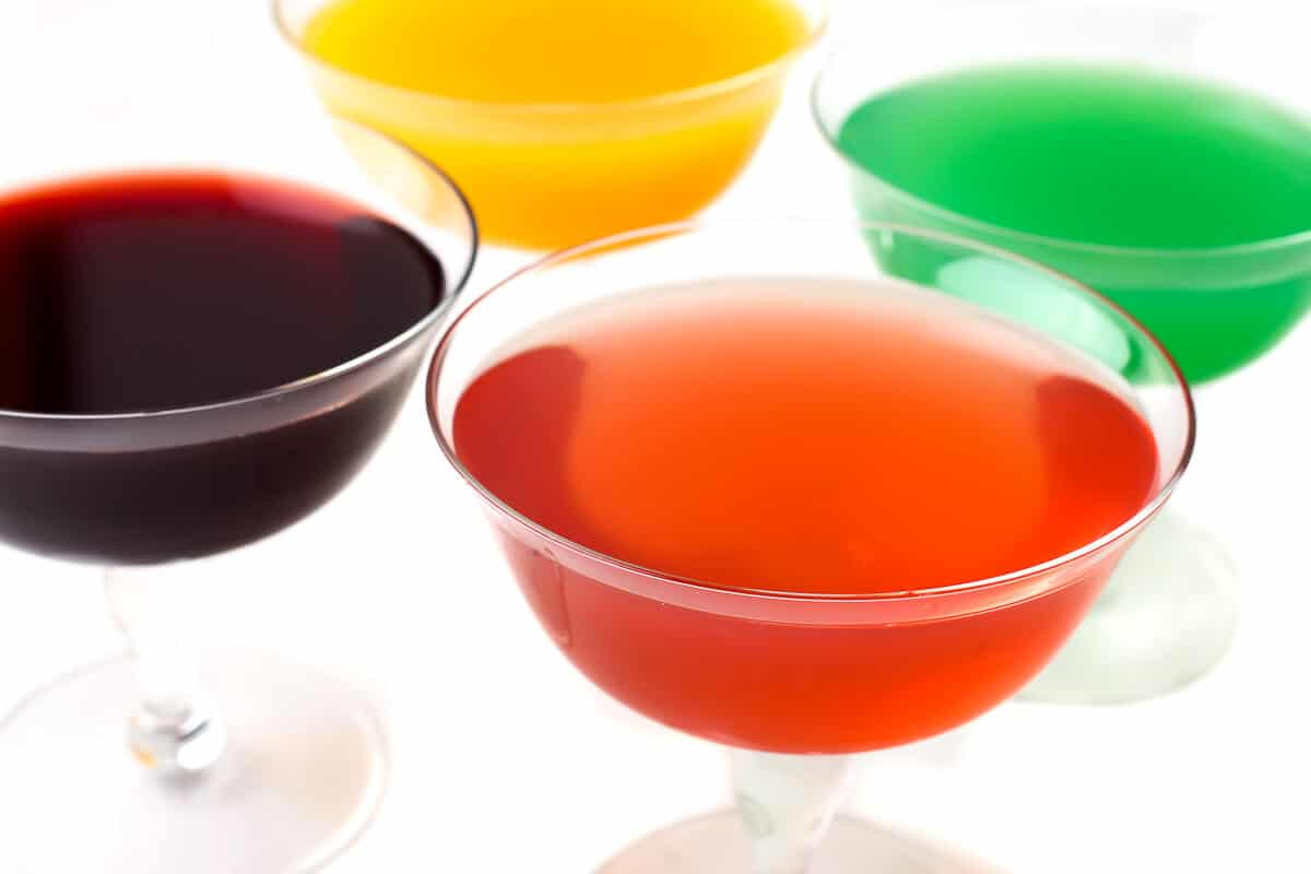 Cuatro vasos de tallo rellenos de diferentes sabores de gelatina vegana hecha con agar agar.