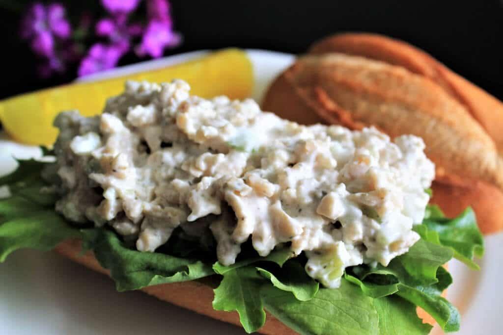 Un sándwich de ensalada de atún abierto hecho con ensalada de atún vegana en un bollo con algo de lechuga.