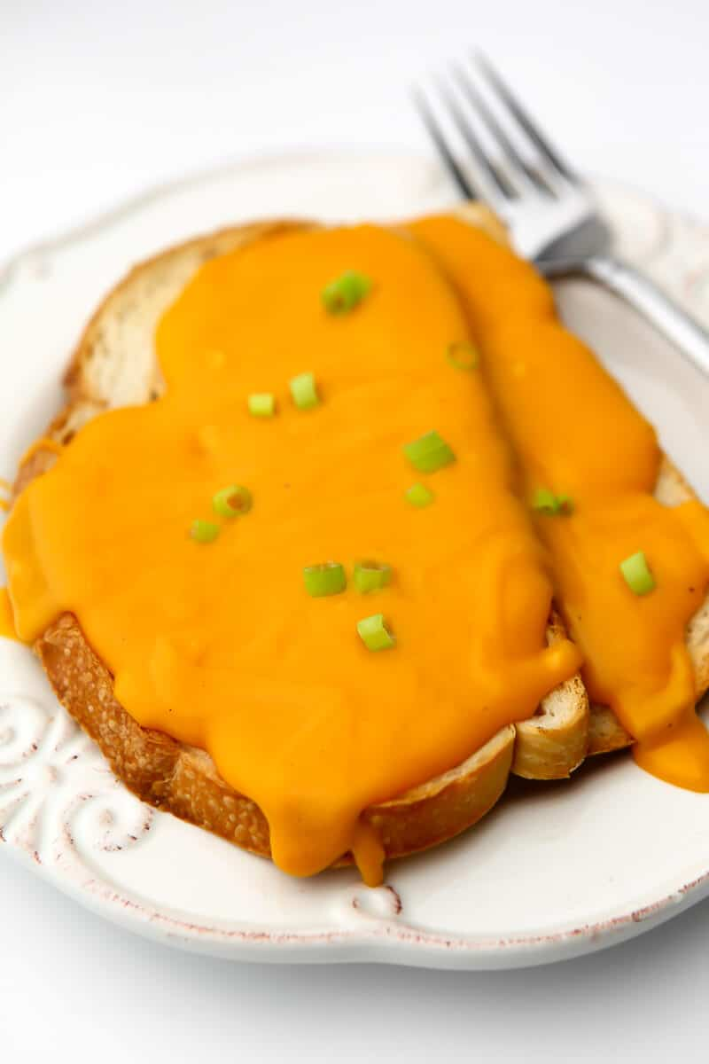 Una salsa Welch Rarebit vegana servida sobre 2 tostadas con un tenedor al lado.