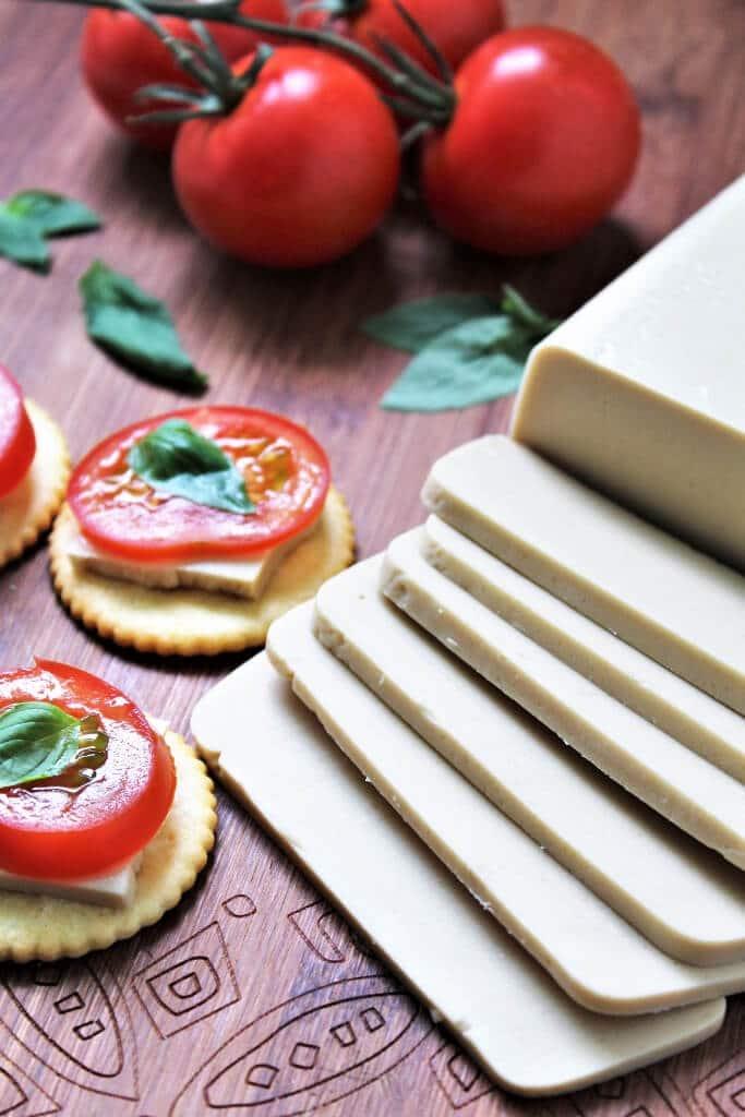Un bloque de queso vegano cortado en una tabla de cortar con tomates detrás.