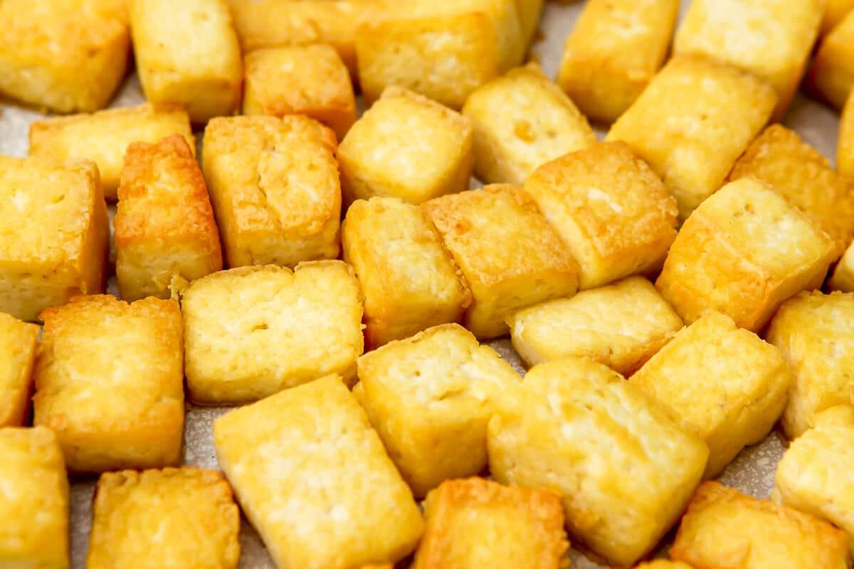 Un primer plano del tofu frito en una sartén blanca.