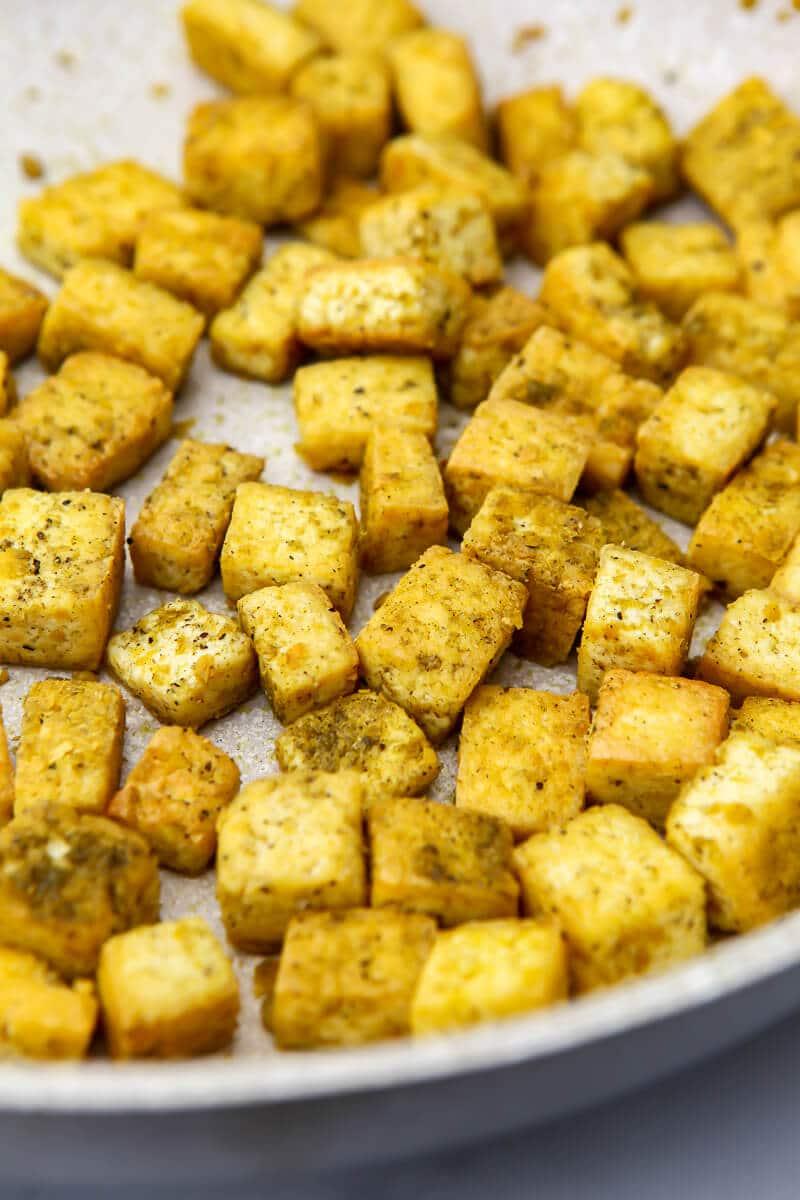 Tofu con sabor a pollo con condimento de ave y levadura nutricional que se fríe en una sartén.