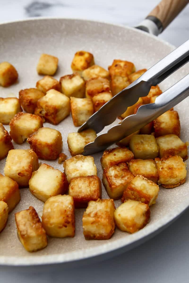 Tofu frito con recubrimiento de almidón de maíz en una sartén al que se le da la vuelta con unas pinzas.