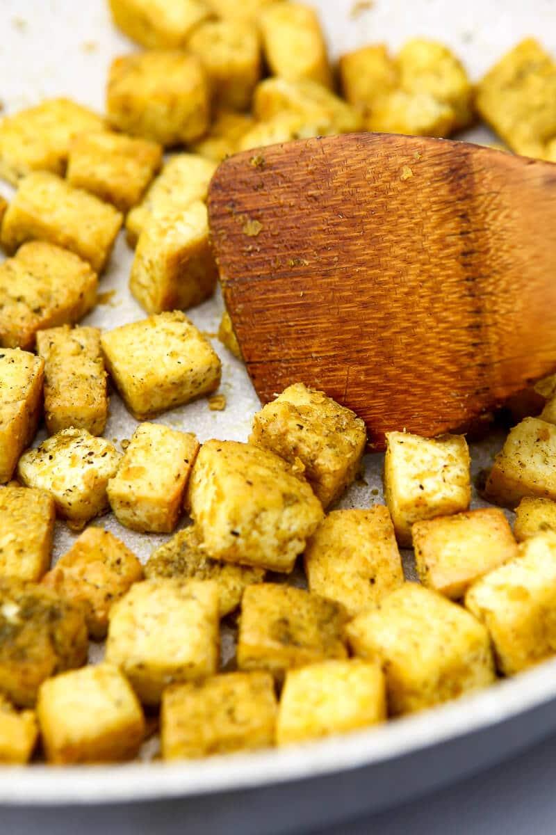 Tofu frito en la sartén con condimento para aves y levadura nutricional.