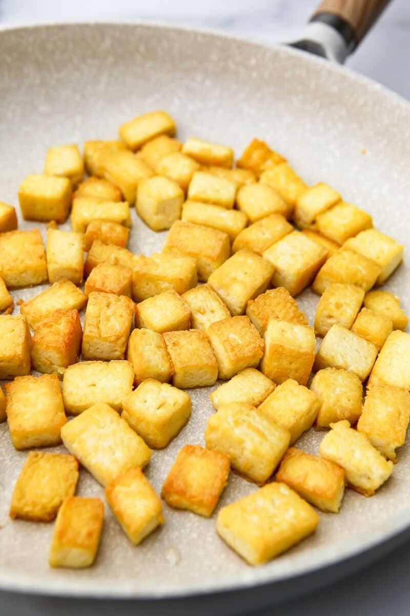 Una sartén llena de cubos de tofu frito.