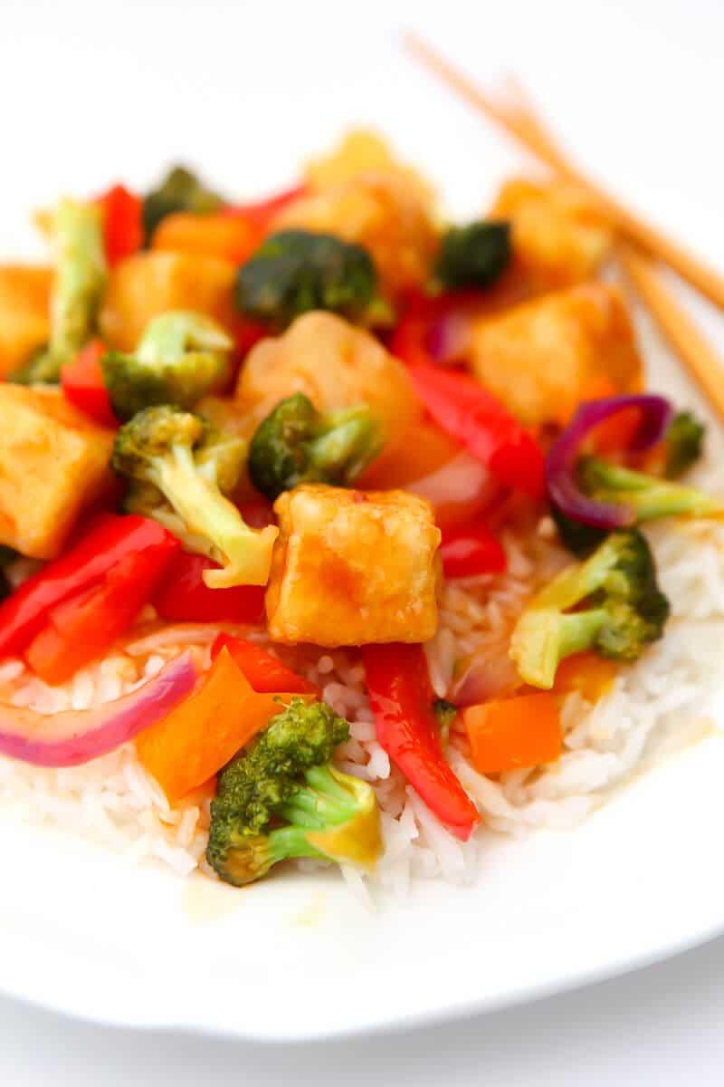 Tofu agridulce con piña, pimiento y brócoli sobre una cama de arroz blanco.