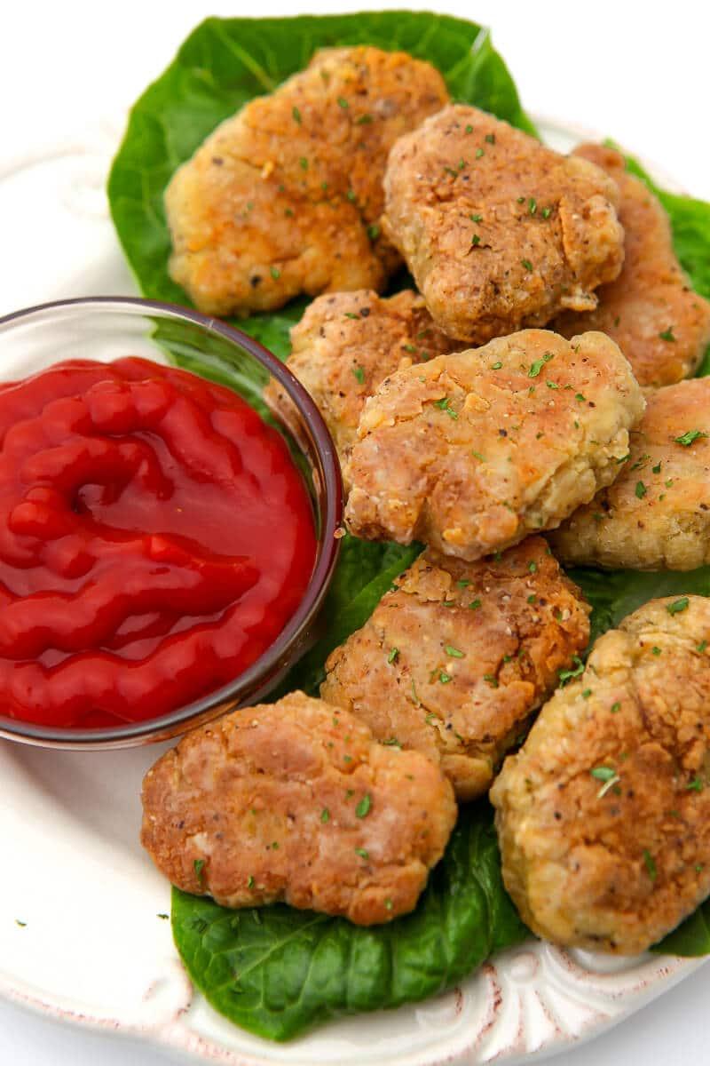 Una vista superior de un plato blanco lleno de nuggets de pollo veganos sobre un lecho de lechuga con ketchup al lado.