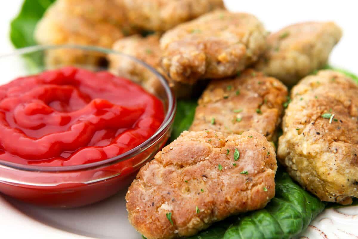 Un primer plano de nuggets de pollo veganos en un plato.