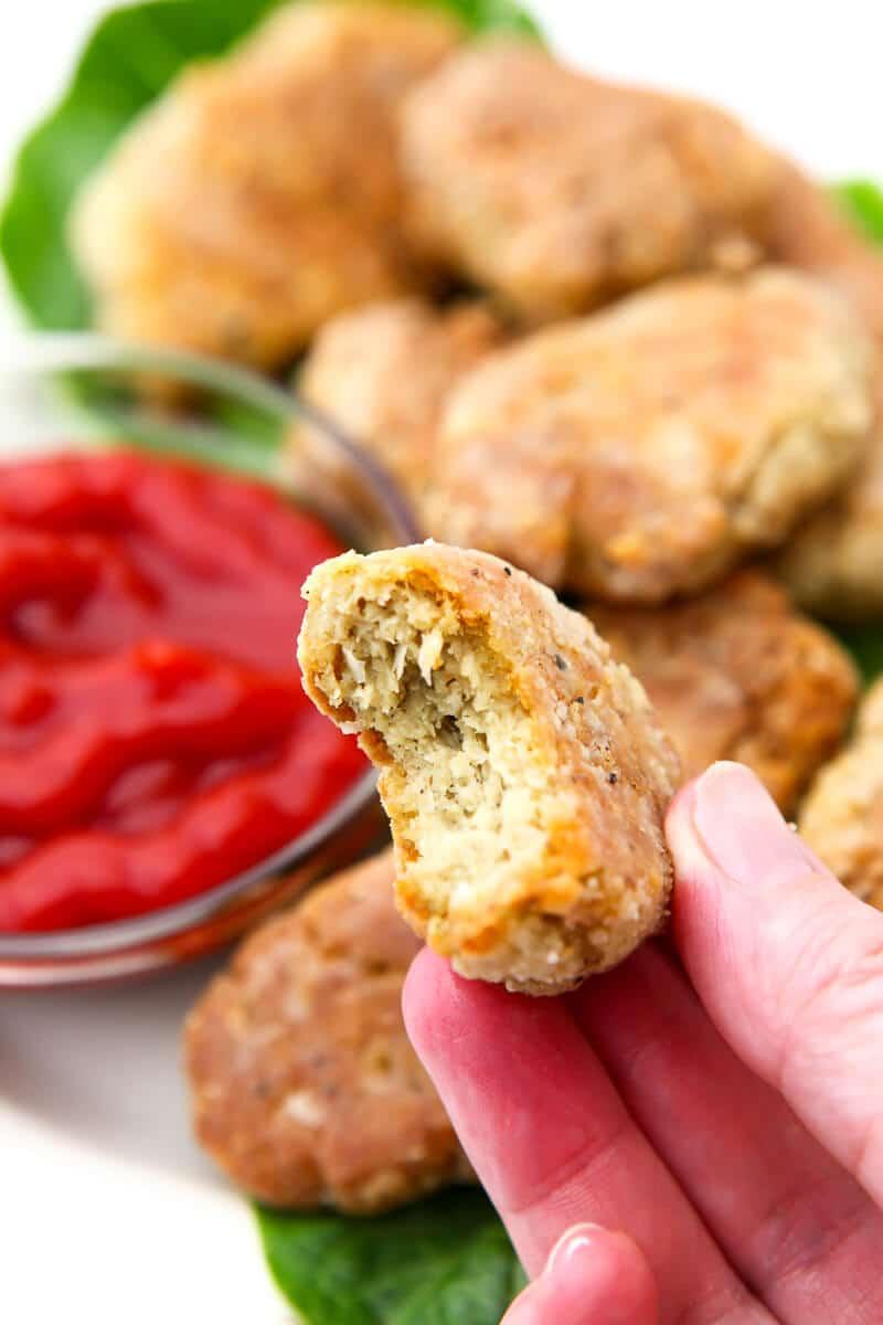 Un nugget de pollo vegano con un bocado en la mano de alguien.