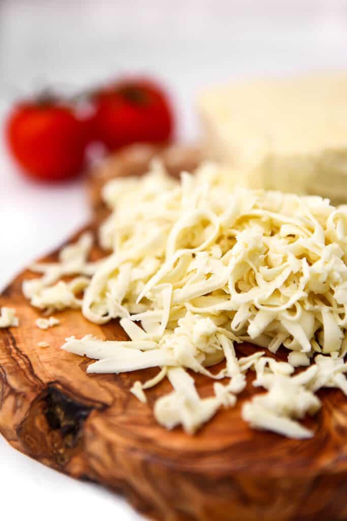 Queso mozzarella vegano rallado sobre una tabla de cortar de madera con dos tomates detrás.