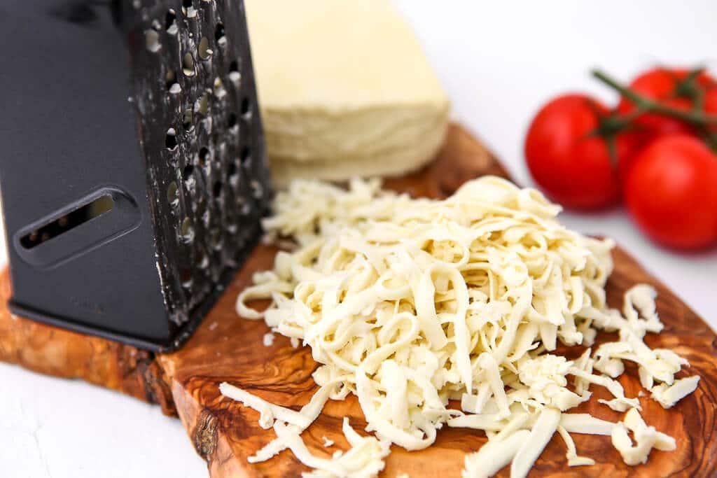 Queso mozzarella sin lácteos en una tabla de cortar con un rallador de queso y un tomate al lado.