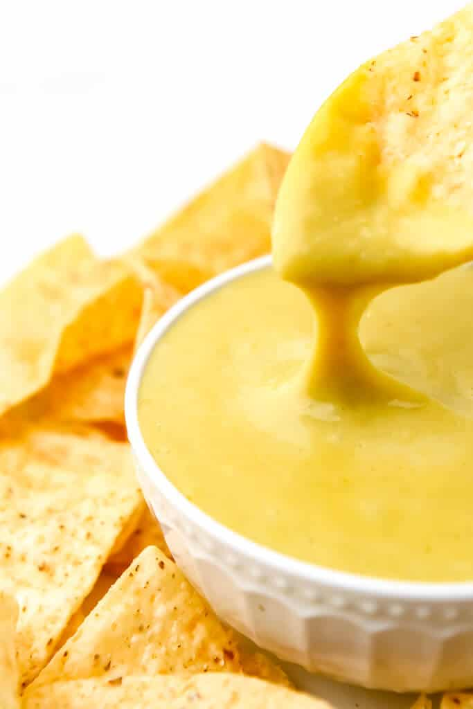 Un chip de maíz siendo sumergido en un tazón de salsa de queso de nacho vegano con queso goteando.